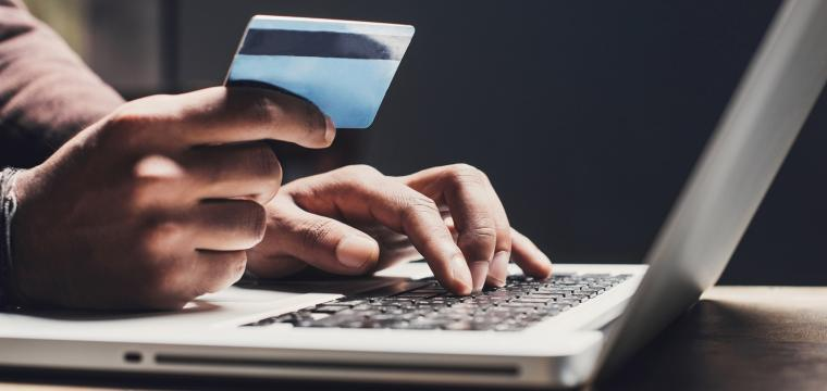 person entering credit card details on computer